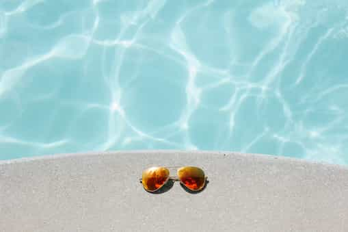 Picture of sunglasses laid by the side of a pool