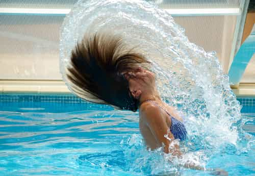 Picture of a woman in a pool swishing her wet hair